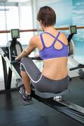 Fit brunette working out on rowing machine - stock photo
