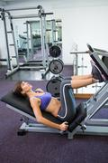 Fit brunette using weights machine for legs - stock photo