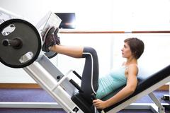 Stock Photo of Fit brunette using weights machine for legs