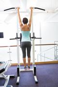 Stock Photo of Fit brunette hanging from bars