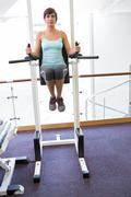 Stock Photo of Fit brunette supporting her weight on bars