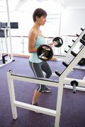 Stock Photo of Fit brunette holding heavy barbell