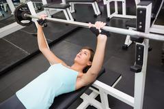 Stock Photo of Fit brunette lifting heavy barbell lying on bench