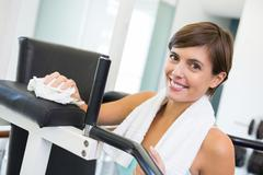 Stock Photo of Fit brunette wiping down bench smiling at camera