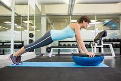 Stock Photo of Fit brunette using bosu ball in plank position