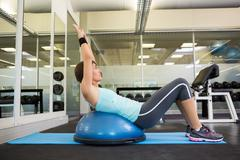 Fit brunette using bosu ball to work out - stock photo
