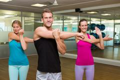 Fitness class led by handsome instructor - stock photo