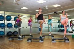 Fitness class doing step aerobics - stock photo