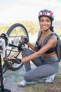 Fit woman fixing the chain on her bike - stock photo