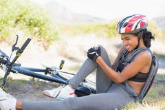 Fit woman holding her injured knee after bike crash Stock Photos