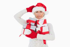 Festive woman scratching head and holding gifts Stock Photos