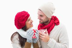 Stock Photo of Attractive young couple in warm clothes holding mugs