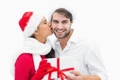 Stock Photo of Attractive festive woman giving boyfriend a kiss and present