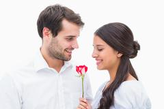 Handsome man offering his girlfriend a rose - stock photo