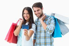 Stock Photo of Attractive young couple with shopping bags and credit card