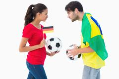 German and brazilian football fan facing off - stock photo