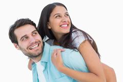 Stock Photo of Happy casual man giving pretty girlfriend piggy back