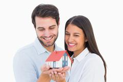 Attractive young couple holding a model house - stock photo
