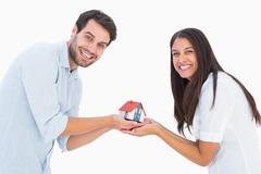 Stock Photo of Attractive young couple holding a model house