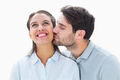 Stock Photo of Handsome man kissing girlfriend on cheek