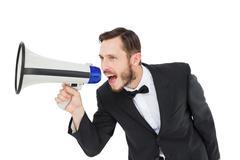 Geeky businessman shouting through megaphone - stock photo