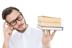 Geeky young man looking at pile of books Stock Photos