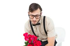 Geeky heartbroken hipster holding roses - stock photo