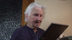 98 Years Old Woman Holding A Photo Of Herself 60 Years Younger, Low Angle Stock Footage