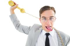 Geeky businessman being strangled by phone cord - stock photo