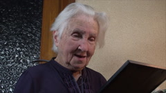 98 Years Old Woman Holding A Photo Of Herself 60 Years Younger, Low Angle, Pan Stock Footage