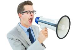 Stock Photo of Geeky businessman shouting through megaphone