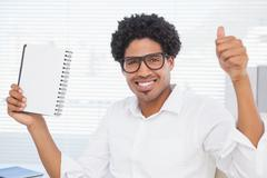 Happy businessman showing notepad and thumbs up Stock Photos