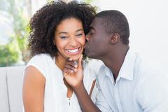 Stock Photo of Attractive man kissing his girlfriend on the cheek