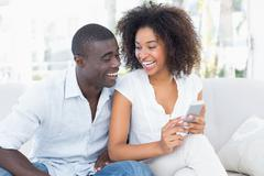 Attractive couple sitting on couch together looking at smartphone Stock Photos