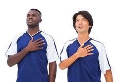 Football players in blue with hands on heart Stock Photos