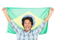 Football fan holding brazil flag and cheering - stock photo