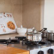Stove top with saucepan and recipe book Stock Photos