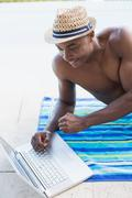 Handsome shirtless man using laptop poolside Stock Photos