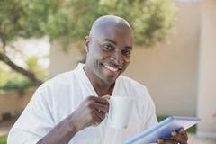 Handsome man in bathrobe using tablet at breakfast outside - stock photo