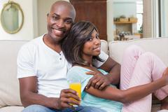 Stock Photo of Happy couple relaxing on the couch with juice