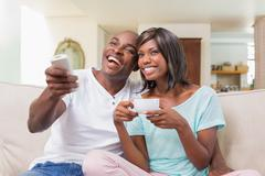 Stock Photo of Happy couple relaxing on the couch watching tv