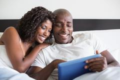 Happy couple cuddling in bed with tablet pc Stock Photos