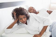Annoyed woman lying in bed with boyfriend Stock Photos
