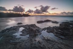 Rocky coast at Treyarnon Bay at sunset, Cornwall, England, United Kingdom Stock Photos