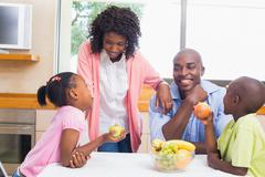 Happy family having fruit together Stock Photos