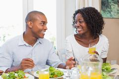 Couple enjoying a healthy meal together smiling at each other Stock Photos