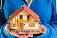 Stock Photo of Hands holding miniature house model