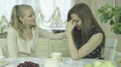 Young elegant woman comforting sad friend at home during tea time Stock Footage