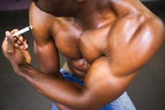 Shirtless muscular man injecting steroids - stock photo