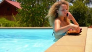 Stock Video Footage of Young Beautiful Woman Talking on Cell Phone and Eating Pineapple in Pool.
